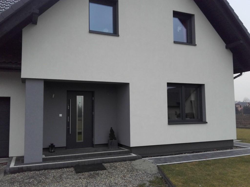 Antracytowe drzwi aluminiowe na tle budynku z antracytowymi oknami