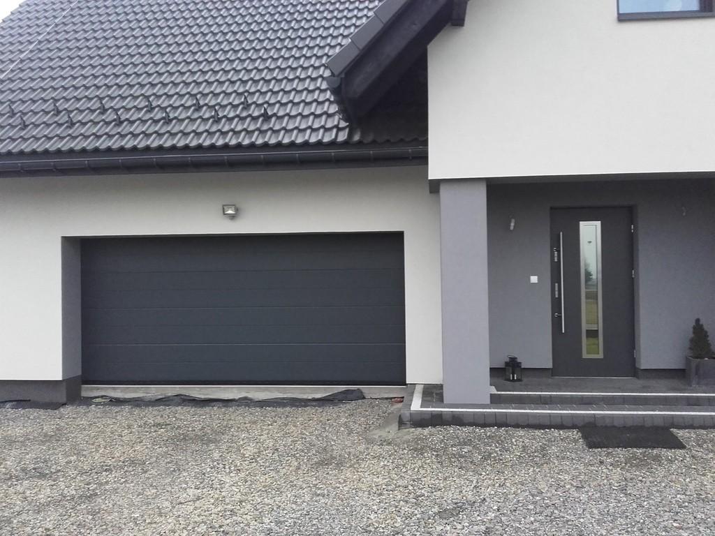 antracytowa brama garażowa z antracytowymi drzwiami zewnętrznymi w biały, budynku