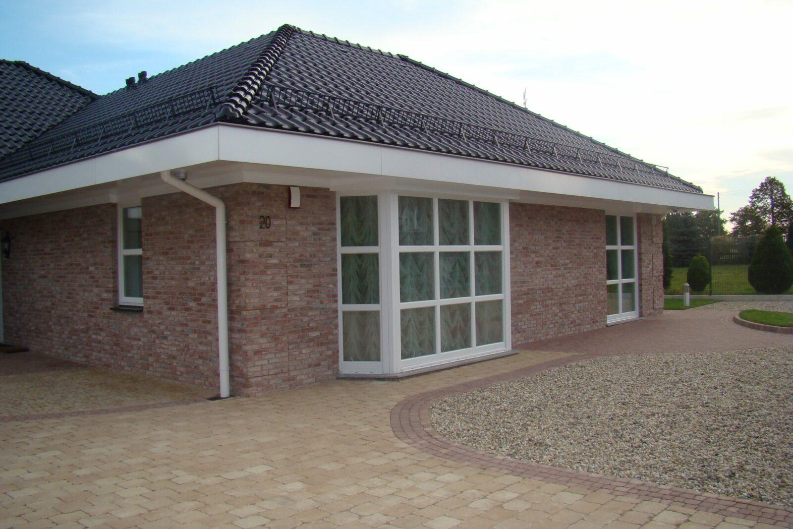 Dom z elewacją ceglaną z białymi oknami ze szprosami i z czarną dachówką