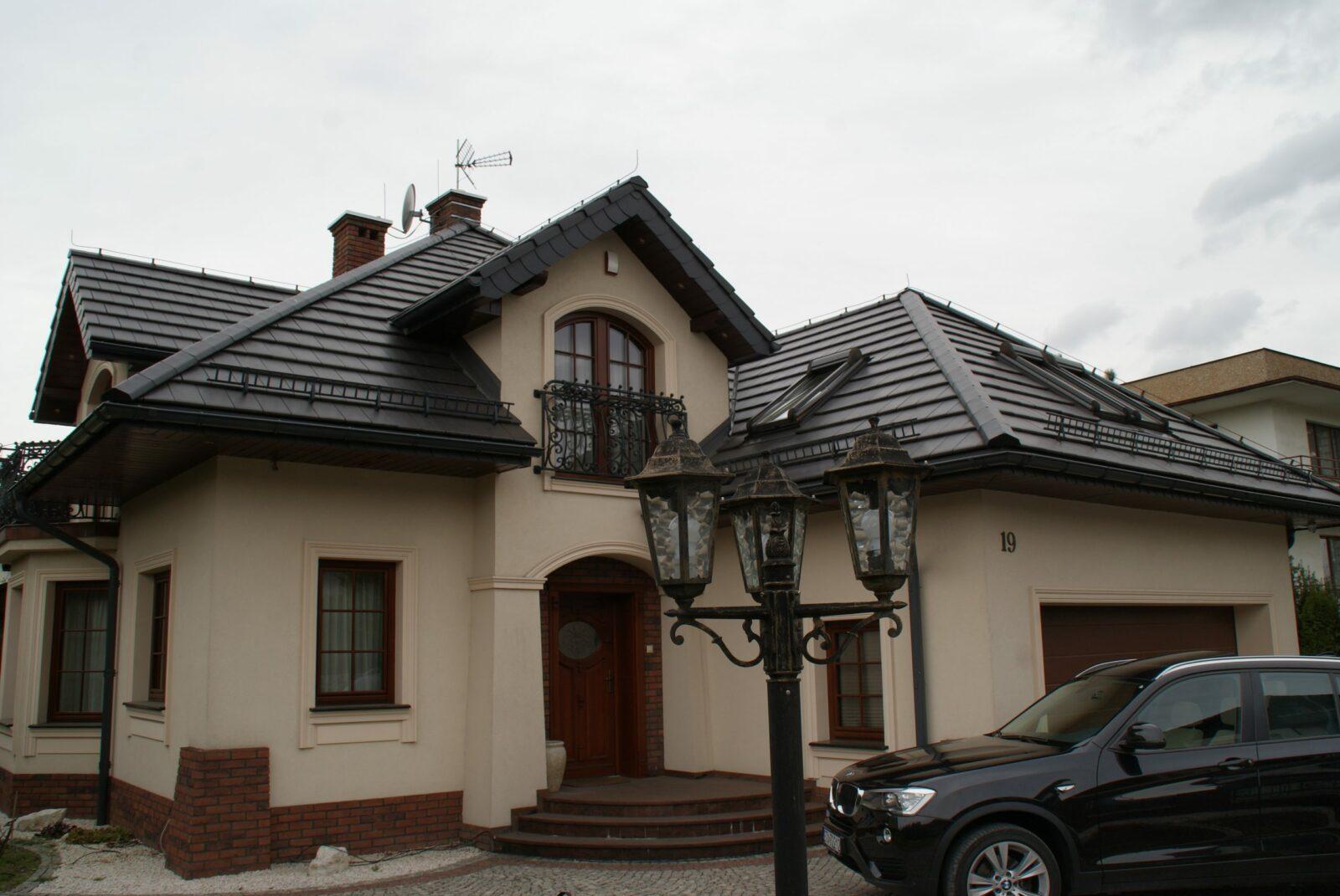 Dom z czarnym dachem z oknami oraz drzwiami obok samochodu