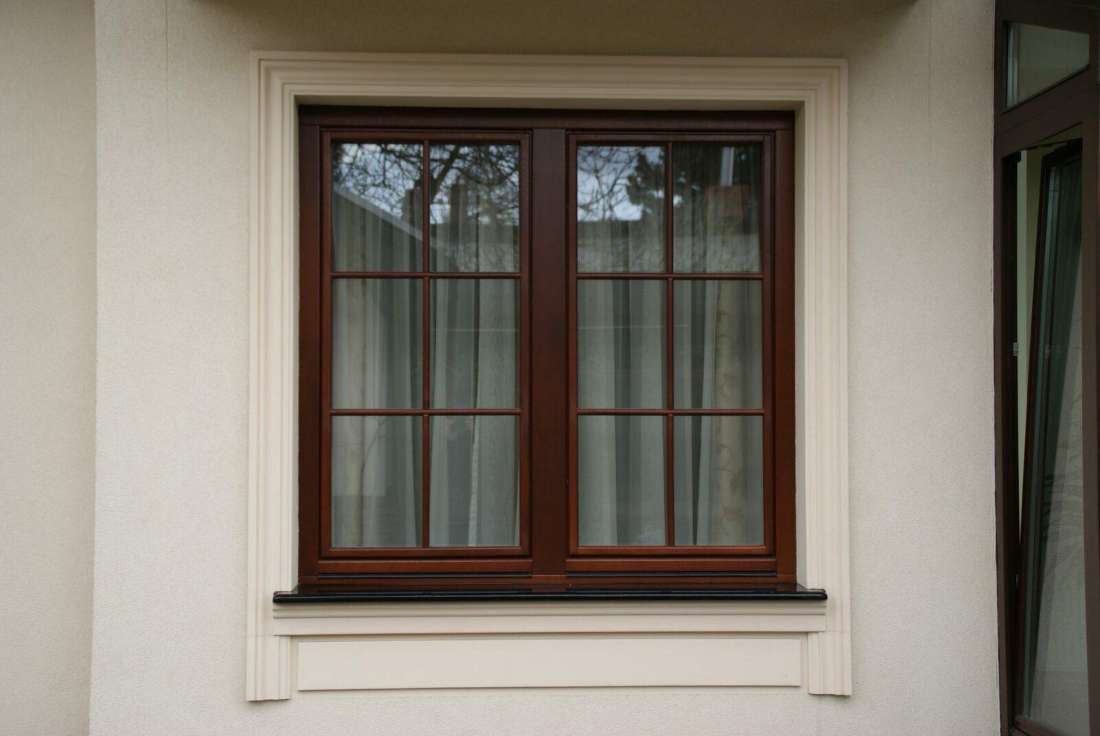 Drewniane brązowe okno na szarej ścianie
