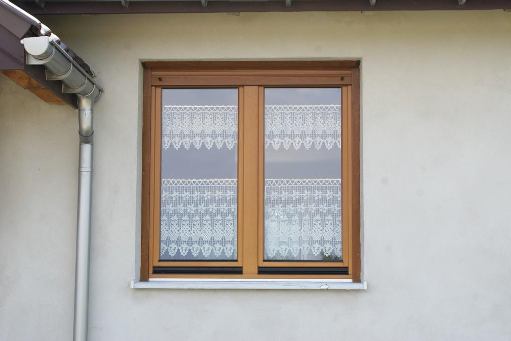 Drewniane okno na białej ścianie