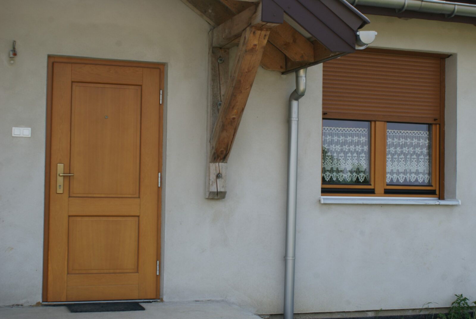 brązowe drewniane drzwi zewnętrzne pod daszkiem domu