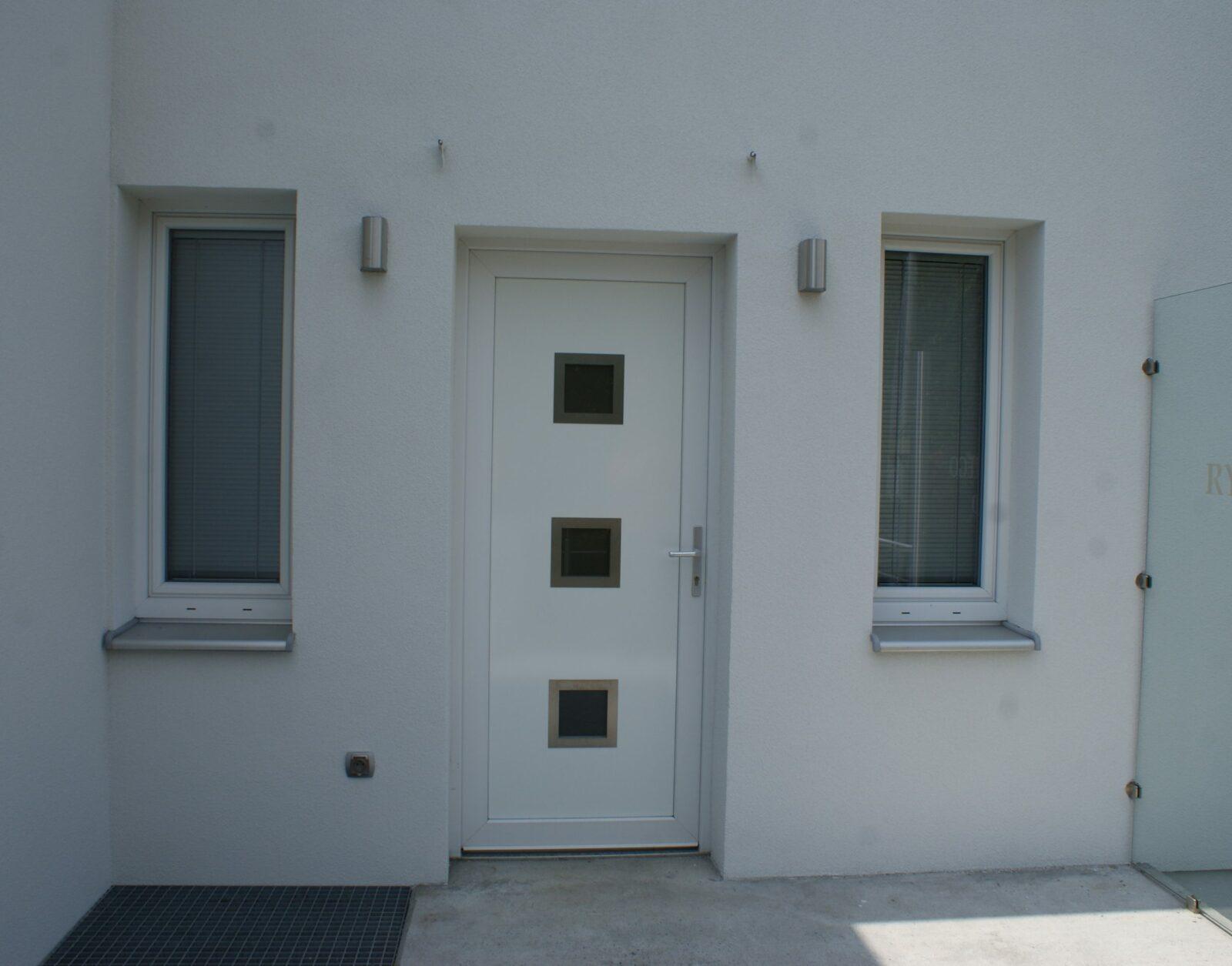białe drzwi zewnętrzne na białej ścianie