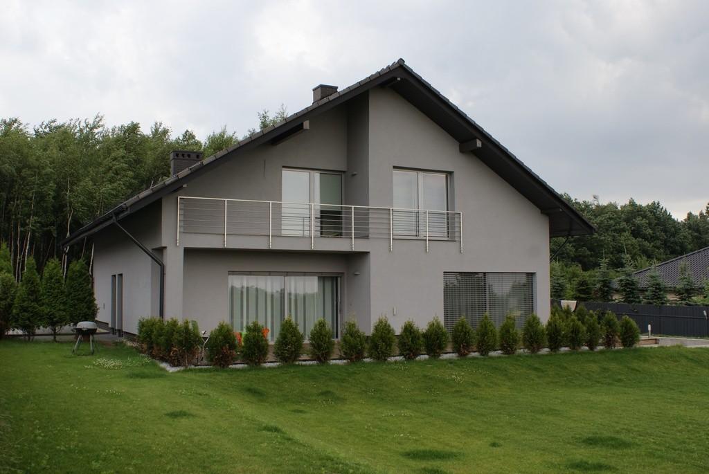 Budynek z aluminiowymi oknami na tle zielonego krajobrazu