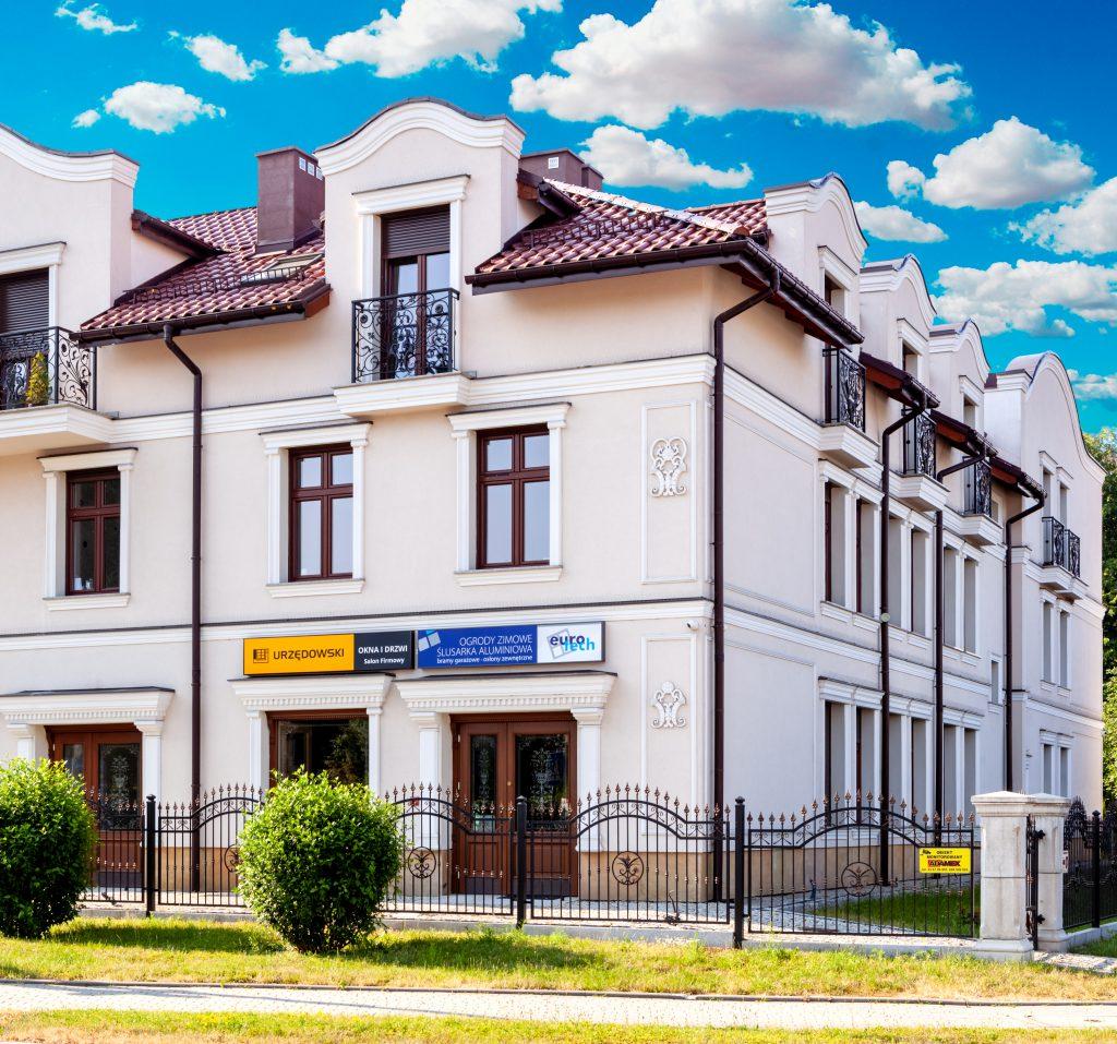 Duża biała kamienica z brązowymi oknami i brązowymi drzwiami na tle niebieskiego nieba