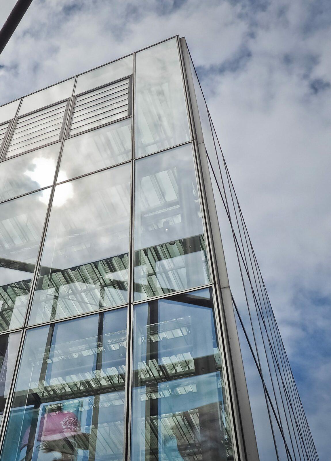 Okno aluminiowe z fasadą na tle niebieskiego nieba z chmurami
