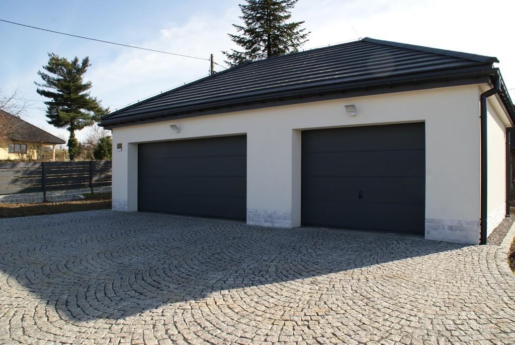 podwójna brama garażowa segmentowa białym garażu z czarną dachówką