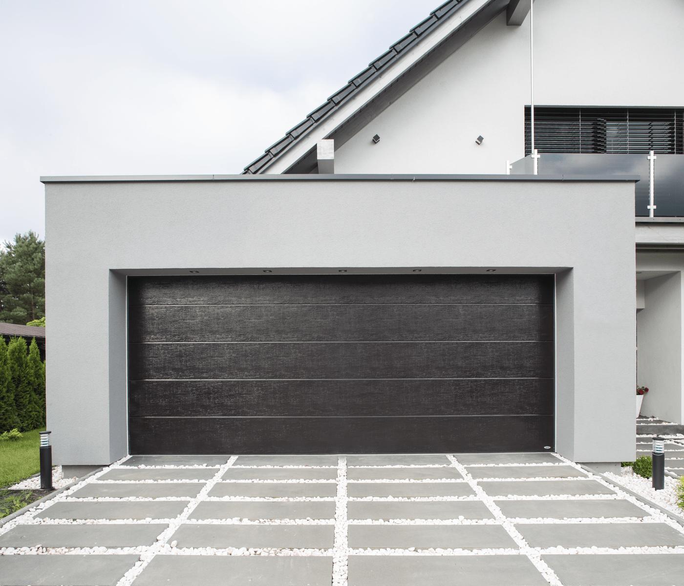 brama garażowa w kolorze antracyt w białym budynku
