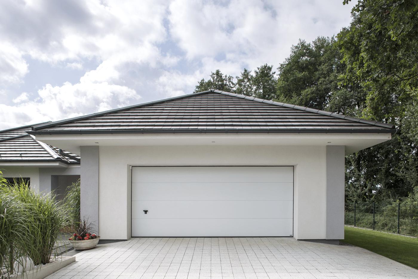 biała brama garażowa w białym garażu z szarą dachówką na zielonym tle