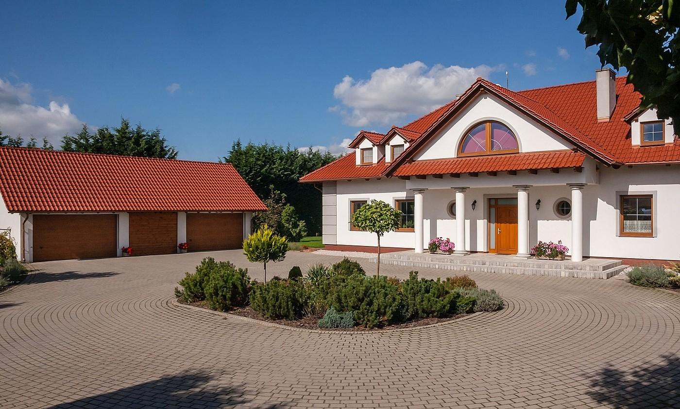 Potrójna brązowa brama garażowa segmentowa obok białego budynku z ceglaną dachówką