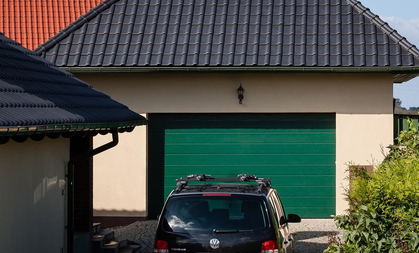 zielona brama garażowa segmentowa a przed nią stoi samochód