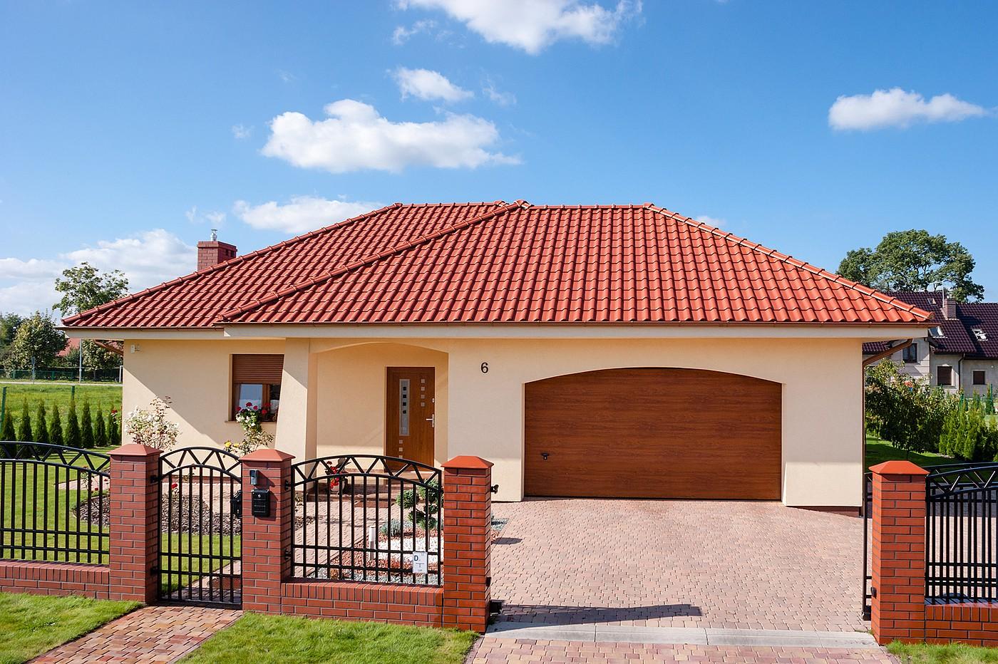 Brązowa brama garażowa na tle beżowego budynku z czerwoną dachówką na tle niebieskiego nieba