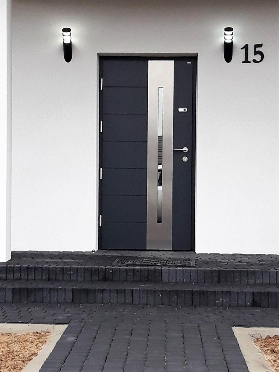 Czarne stalowe drzwi zewnętrzne na białej frontowej ścianie