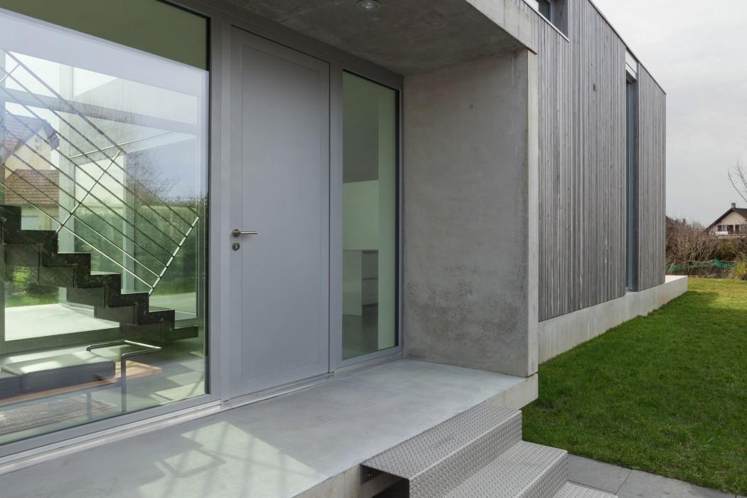 Szare aluminiowe drzwi zewnętrzne obok dużego przeszklenia na zewnątrz szarego domu