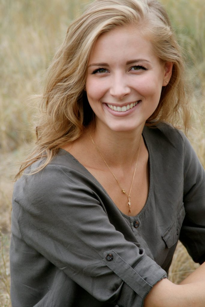 Uśmiechnięta kobieta z blond włosami , z szarą bluzką na tle żółtej trawy