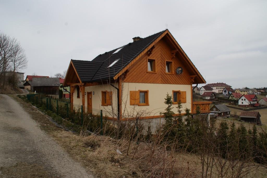 Duży budynek z brązowymi drewnianymi oknami na tle innych budynków