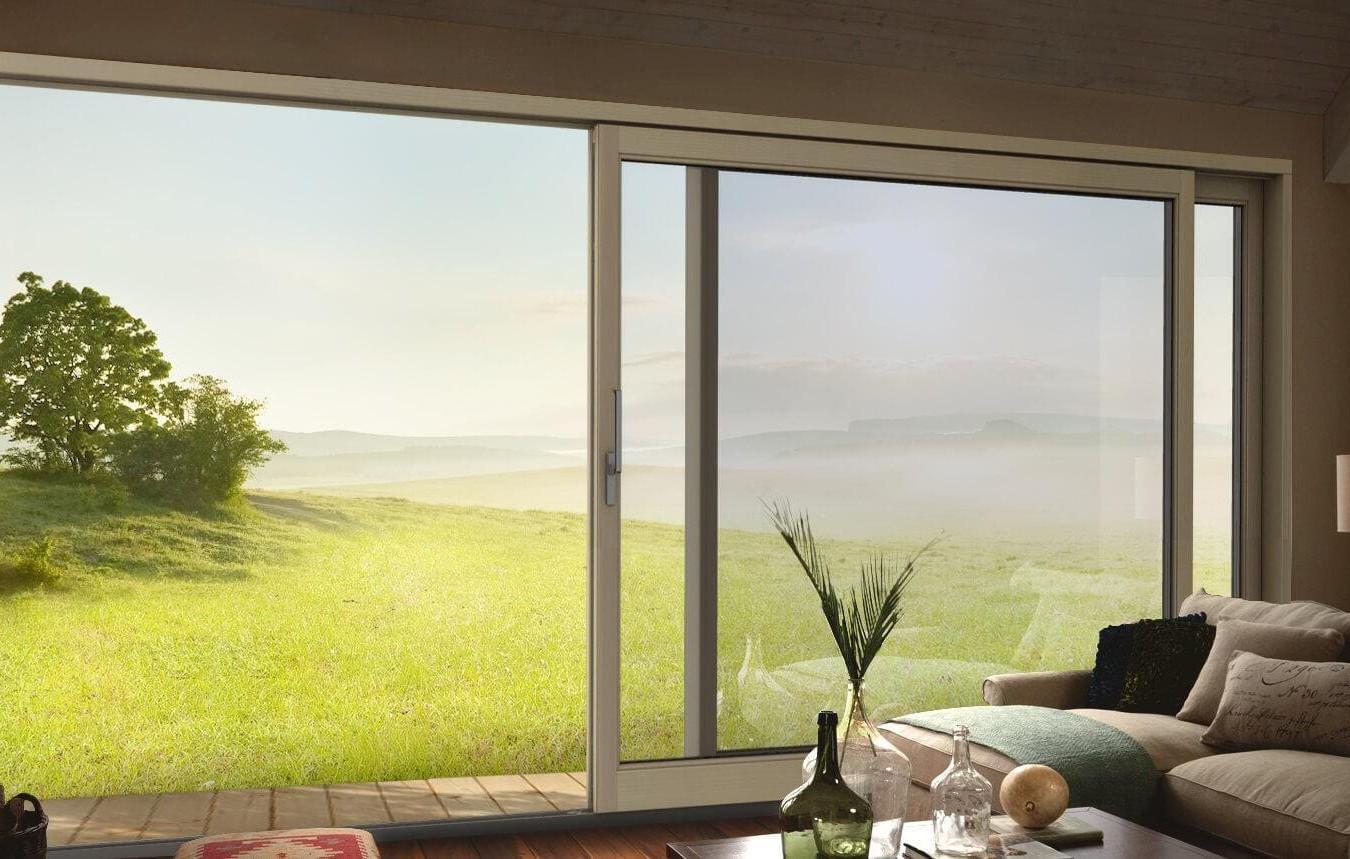 Wielki okno w salonie z widokiem na zieloną łąkę z drzewem po lewej stronie