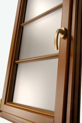 drewniane okno z szybami z złotą klamką na białym tle