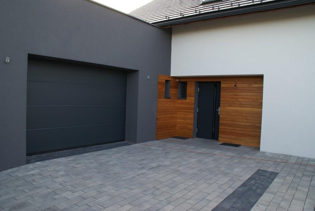 antracytowa brama garażowa z antracytowymi drzwiami na tle białego budynku