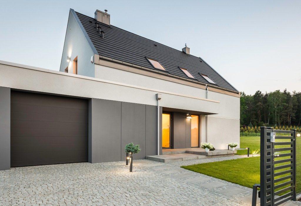 Biały dom z szarą bramą garażowa, drzwiami zewnętrznymi oraz oknami dachowymi